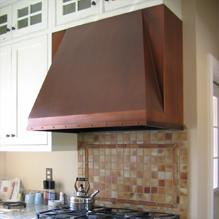 Copper Range Hood with riveted strapping detail and a medium antique finish