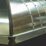 Galvanized steel island range hood accented with iron hip caps, and vertical strapping details with decorative iron rivets